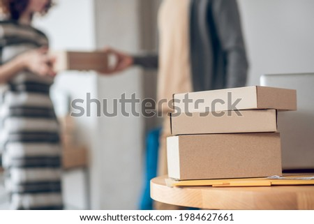 Woman in a striped dress receiving the delivery from a courrier Photo stock ©