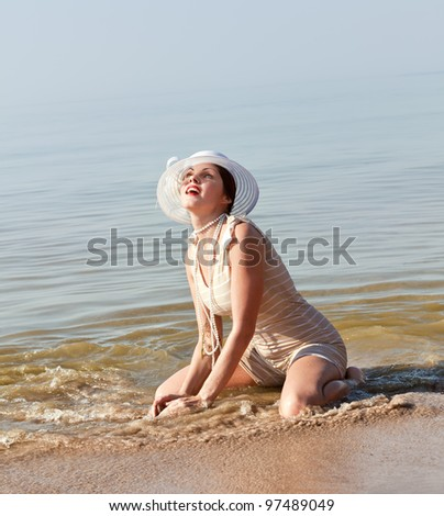 Woman in a striped retro bathing suit kneeling in the water at the beach