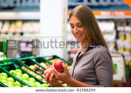 Woman in a supermarket at the shelf for fruits shopping for groceries, she is checking out the apples
