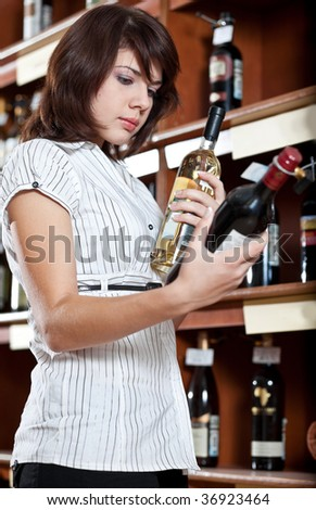 woman in a supermarket comparing two wines