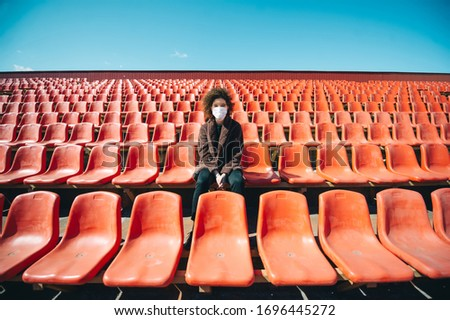 Woman in a surgical mask sitting in an empty stadium during epidemic disease Covid-19. Curly girl in mask alone in stadium is scared.