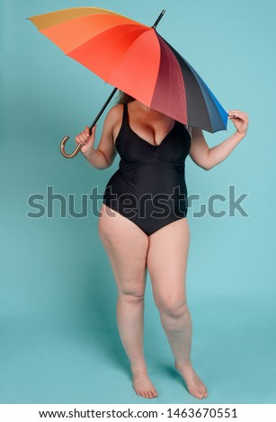 Woman in a swimsuit covering her face with an umbrella on blue background. She's ashamed of her obese body. #1463670551