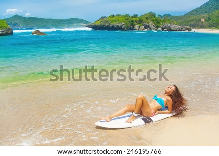 Stock Photo Woman in a swimsuit resting over a surf boar on a beach