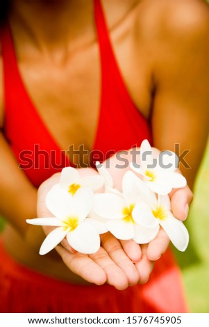 Woman in a tropical setting holding frangipani.