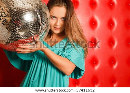 woman in a turquoise dress, stands beside a red leather wall. flowing hair, bare shoulder. holding a mirror ball