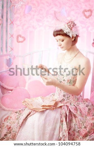 Woman in a vintage dress with old letters in her hand.