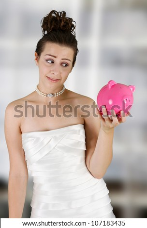 Woman in a wedding dress holding piggy bank