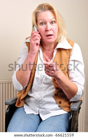 woman in a wheelchair is talking on a telephone