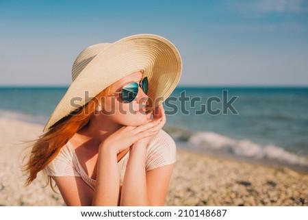 woman in a wide sun hat enjoying the summer sun at the beach