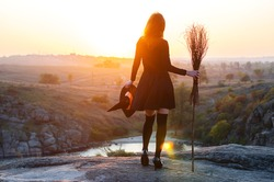 Woman in a witch costume with a broom and hat, a background of halloween. The witch looks at the sunset, free space.