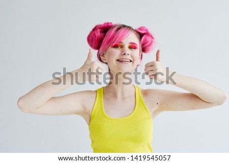 woman in a yellow shirt with pink hair is sitting #1419545057