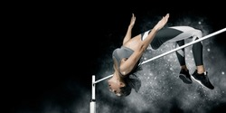 Woman in action of high jump on smoke background. Sports banner. Horizontal copy space background