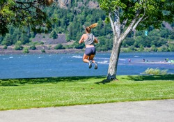 Woman in activewear engaged in jumping training on the picturesque bank of the river, preferring active lifestyle to improve the health and keep a toned slim figure and strengthen the immunity