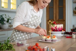 woman in an apron decorates cupcakes with strawberries. pastry chef in the kitchen makes desserts, cakes and muffins. Cooking at home