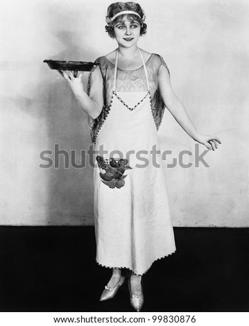 Woman in an apron holding a plate of food and smiling