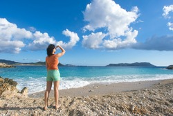 Woman in an orange T-shirt and shorts looking into the distance on the seashore
