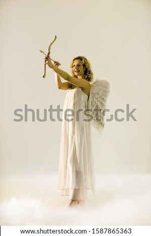 Woman in angel outfit aiming cupid's bow and arrow