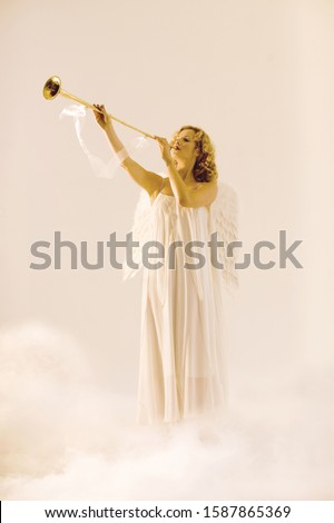 Woman in angel outfit blowing horn