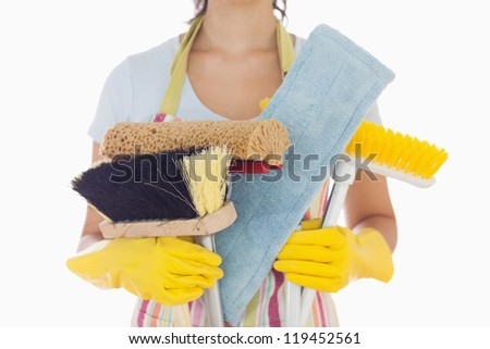 Woman in apron and rubber gloves holding brushes and mops