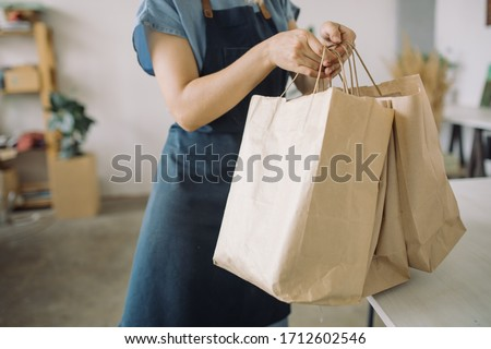 Woman in apron packaging products in paper bags for sale in workshop. Small business concept.
