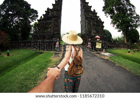 Woman in asian dress and hat holding man by hand travelling Asia. Pov view Foto stock ©