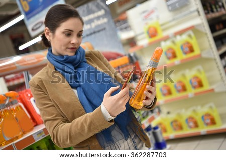 Woman in auto repair shop scanning products with smartphone