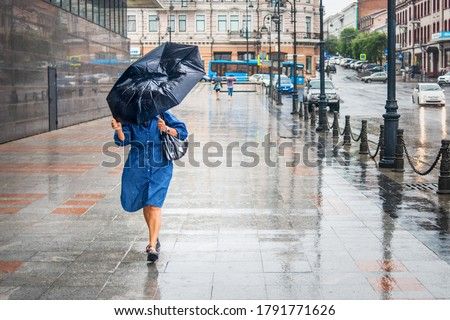 Woman in bad rainy weather walks down the street and tries to keep the umbrella from the strong wind. City landscape in rainy weather. City scenes in the rain. Foto stock ©