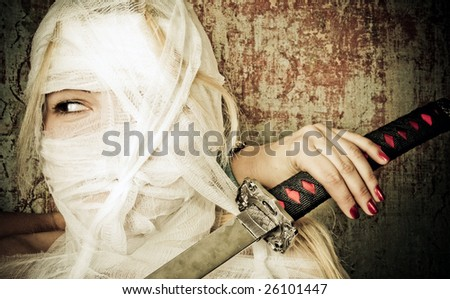 Woman in bandage on the dirty background with a japanese sword