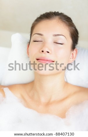 Woman in bath relaxing. Closeup of young asian woman in bathtub bathing with closed eyes.