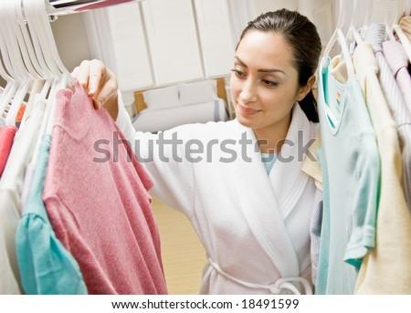 Woman in bathrobe looking in closet for clothing