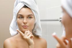 Woman in bathroom is applying moisturizing and anti-aging cream under her eyes