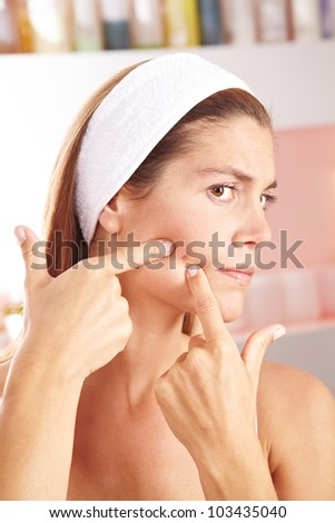 Woman in bathroom squeezing pimple on her cheek