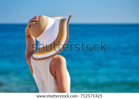 Woman in beach hat against the sea. #712571425