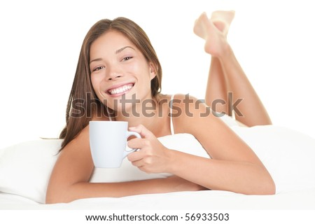Woman in bed drinking tea. Woman enjoying tea in the bed in the morning. Beautiful mixed race Chinese Asian / Caucasian female model lying in bed isolated on white background.