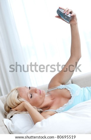woman in bed holding alarm clock and waking up