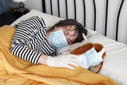 Woman in bed with latex gloves and mask by covid-19 in bed with a stuffed puppy with mask during the covid-19 quarantine