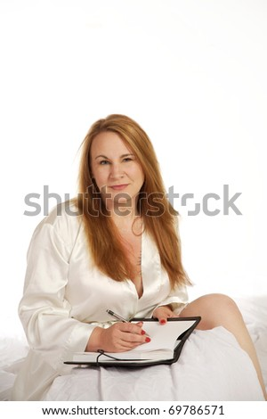 Woman in bed writing in her journal or diary