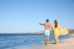 Woman in bikini and her boyfriend on beach, back view with space for text. Lovely couple