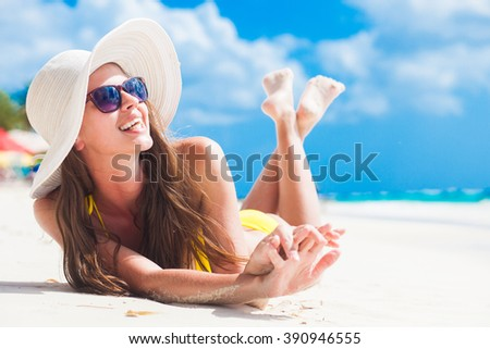 woman in bikini and sun hat relaxing at sunny beach. remote tropical beaches and countries. travel concept #390946555