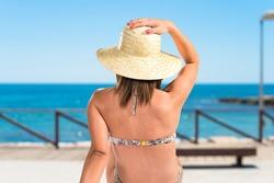 woman in bikini in back position at the beach