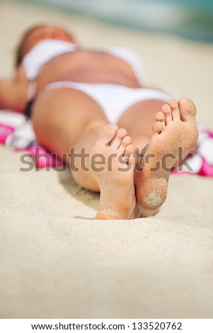 woman in bikini lying and sunning on the beach