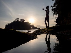 Woman in bikini on shoreline looking at sunset and island. reflection of woman in water.