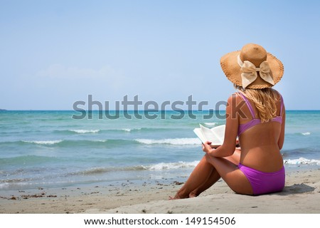 woman in bikini reading book on the beach