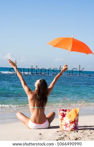 woman in bikini sitting on the beach arms in the air