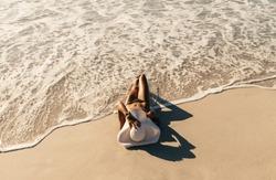Woman in bikini sunbathing lying near the seashore wearing sun hat with sea waves touching her. Woman on vacation wearing sun hat relaxing at the beach.