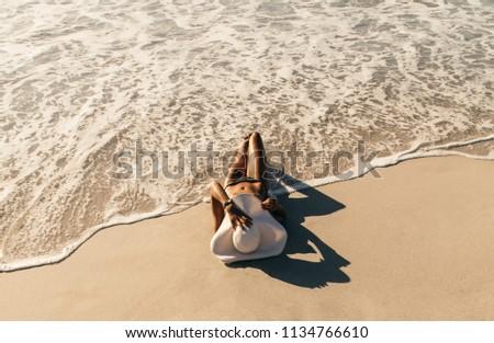 Woman in bikini sunbathing lying near the seashore wearing sun hat with sea waves touching her. Woman on vacation wearing sun hat relaxing at the beach. #1134766610
