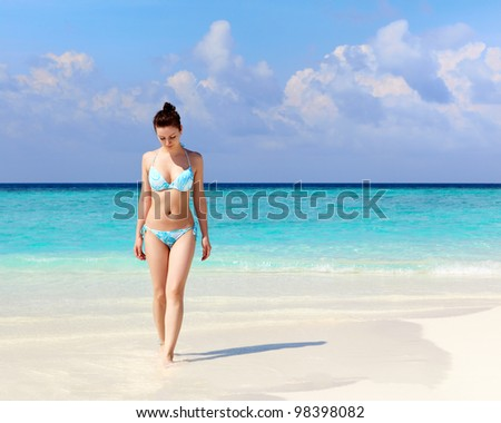 Woman in bikini walk on a beach against the sea