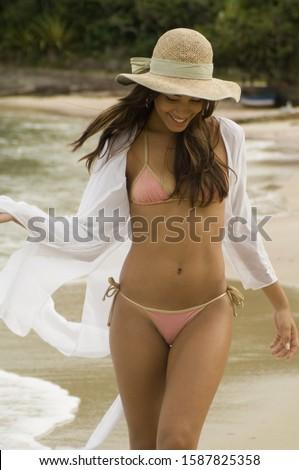 Woman in bikini walking next to water