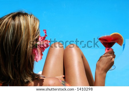 Woman in bikini with cocktail by bright blue pool