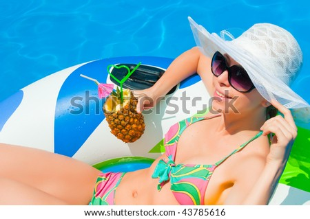 stock photo : Woman in bikini with cocktail by bright blue pool